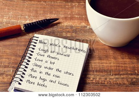 a cup of coffee and a notebook with a list of new years resolutions, such as laugh at yourself, give flowers, love a lot, sleep under the stars or run in the rain, on a rustic wooden table