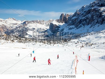 Skiers going down the slope at Sella Ronda ski route in Dolomites, Italy