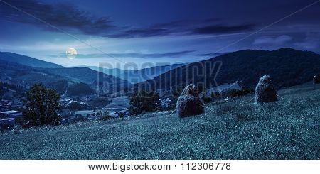 Haystacks On Hillside Near The Village At Night
