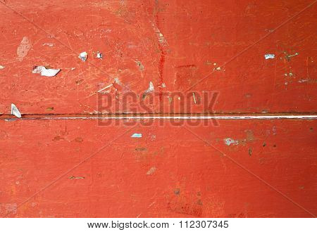 Closeup of red wooden texture of board with staples and scarp of paper.