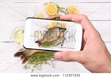 Hands taking photo fish with smartphone.