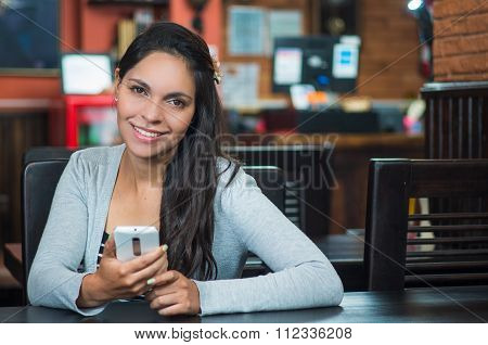 Attractive brunette wearing grey sweater sitting by restaurant table holding mobile phone ad smiling