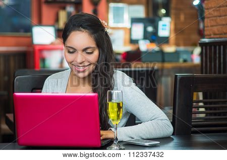 Attractive brunette wearing grey sweater sitting at restaurant table working with pink laptop and gl