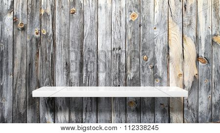 Empty white wall shelf on old planked wall.