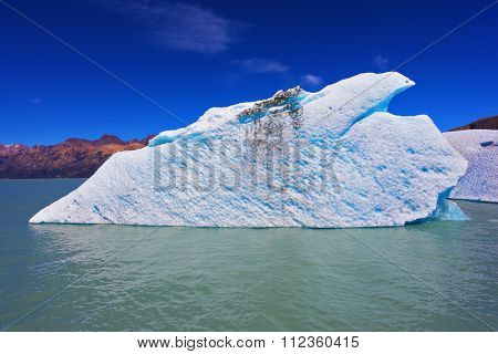 Excursion on the tourist boat on Lake Viedma. White and blue huge icebergs floating near the ship broadside. Ice and sun Patagonia, Argentina