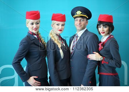 MOSCOW - JUL 09, 2015: Portrait of a crew of three beautiful flight attendants in red hat and one steward at DME RUNVAY in Domodedovo