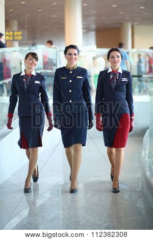 MOSCOW - JUL 09, 2015: Three beautiful women shows a uniforms flight attendant at a special screening of uniforms airlines DME RUNVAY in Domodedovo