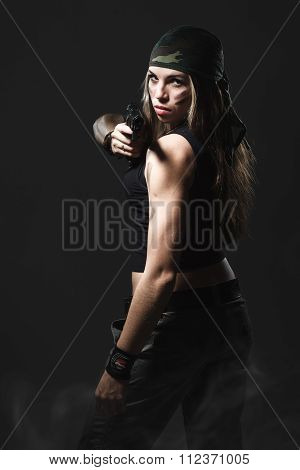 Sexy woman holding gun with smoke studio shot