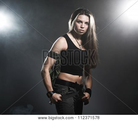 Sexy woman holding daggers with smoke. studio shot