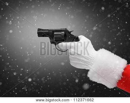 Hand in costume Santa Claus is holding gun / studio shot of man's hand holding loaded gun / Merry Christmas & New Year's Eve concept / Closeup on dark black background.