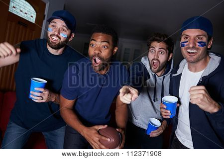Group Of Male Sports Fans Watching Game On Television