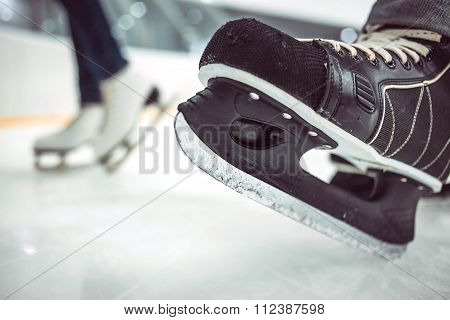 Man's hockey skates and women's figure skates on ice background