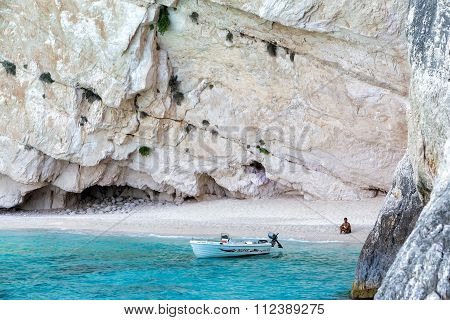 Tourist Sitting On The Beach Of Zakynthos Island, In Greece.