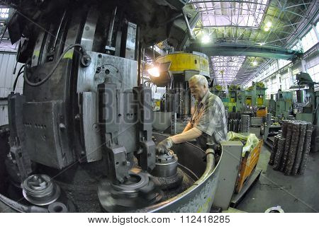 Elderly worker watches on milling machine work