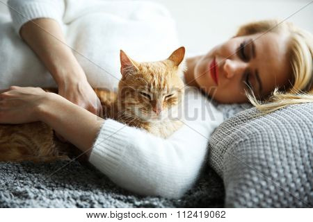 Attractive woman laying with red cat
