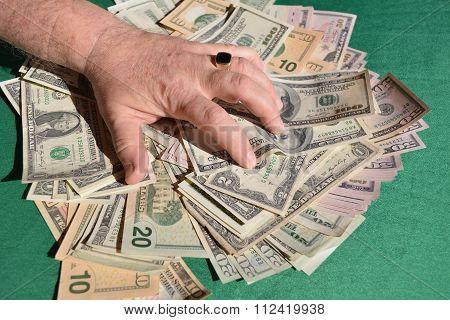 man's hand squeezes dollar bills