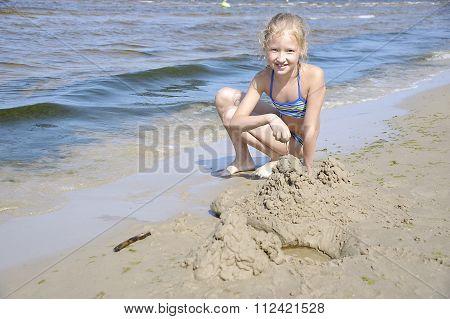 Jurmala. Girl Playing With Sand On The Beach.
