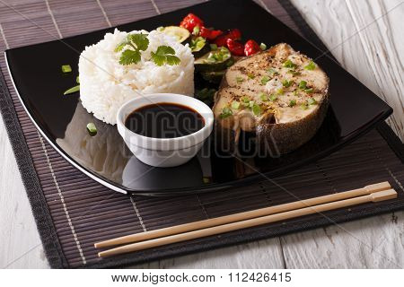 Baked Fish, Rice, Vegetables And Soy Sauce On A Plate Close-up