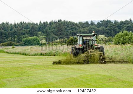A tractor being used to cut grass