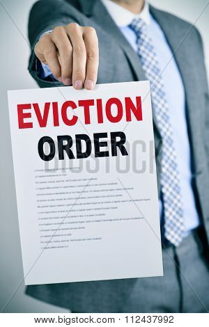 a young caucasian man wearing a gray suit shows a document with the text eviction order