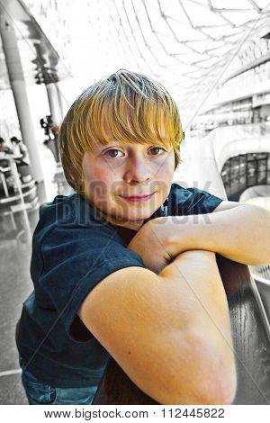 Boy Resting At A Balustrade In A Modern Shopping Center