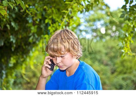 Young Boy Talking On A Cell Phone