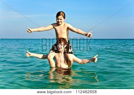 Brothers Are Enjoying The Clear Warm Water At The Beautiful Beach And Playing Pickaback