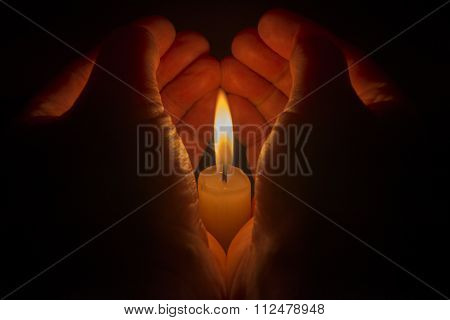 Protective Hands Around A Burning Candle.