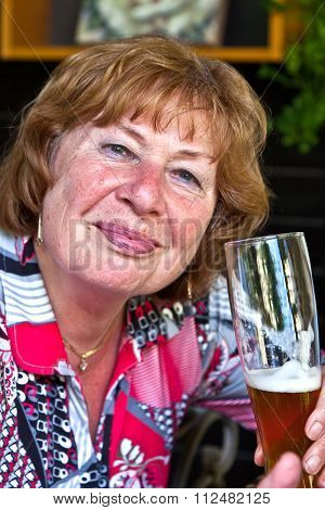Attractive Elderly Lady Enjoys Drinking A Beer In A Beergarden