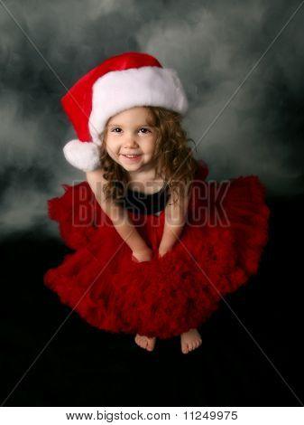 Little Girl Wearing Christmas Santa Hat And Red Pettiskirt