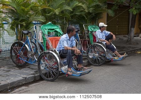 Cyclo drivers waiting for passenger on the side of a street in Hoi An ancient town