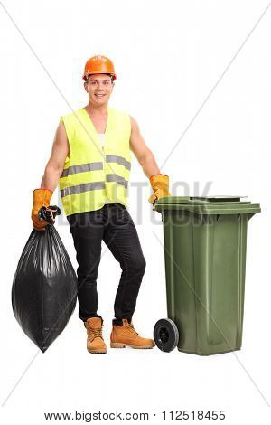 Full length portrait of a young male waster collector emptying a trash can isolated on white background