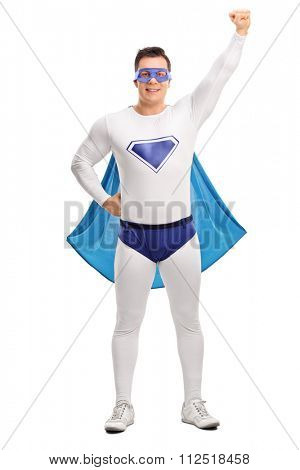 Full length portrait of a young superhero with a blue cape raising his hand in the air isolated on white background