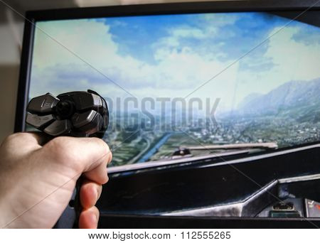 Hand on joystick, playing flight simulator