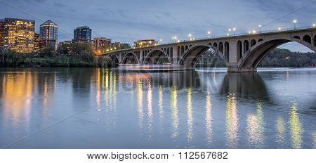Dusk over Key Bridge and Rosslyn from Georgetown in Washington DC, USA. The Key Bridge spans the Potomac River, connecting the Georgetown neighborhood in the District of Columbia with the neighborhood of Rosslyn in Arlington County, Virginia.