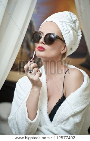 Portrait of beautiful woman with sun glasses applying the lipstick in spa and wellness salon