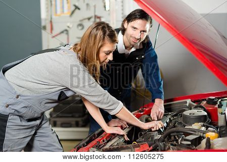 Auto mechanic guiding a female trainee in garage
