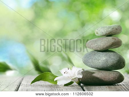Spa stones on table,  on green nature background