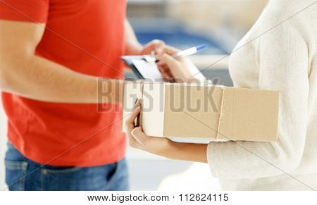 Woman signing receipt of delivery package, close up poster