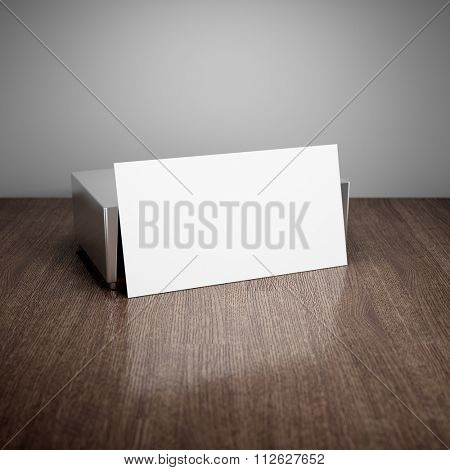 Blank business card with aluminum holder on wooden table