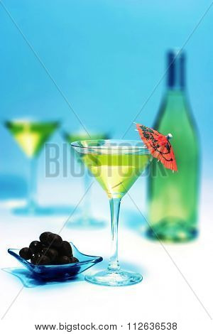 martini glass with black olives