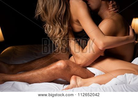 Man kissing woman while she is on top of him