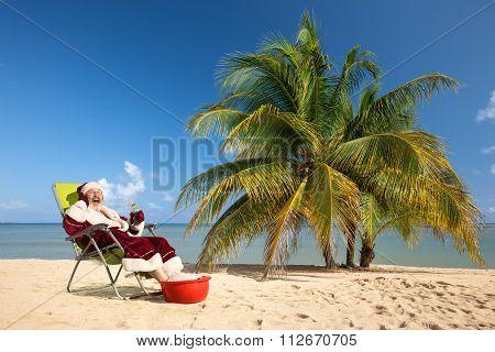 Santa Claus sitting in deck chair on beach