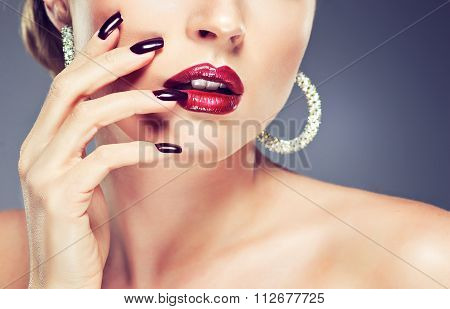 Beautiful girl showing Burgundy manicure and stylish jewelry