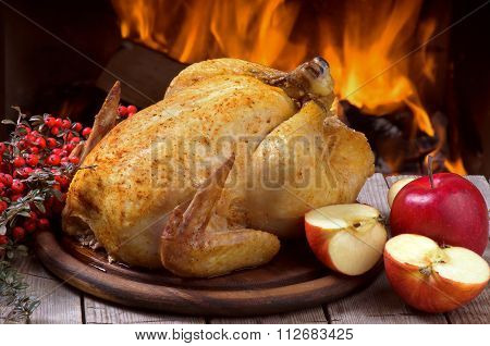 Baked chicken with apples on wooden table.
