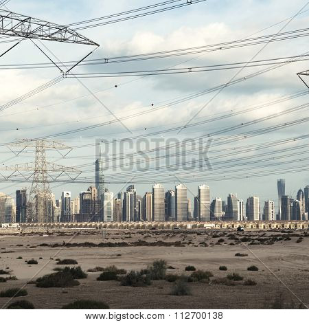 High voltage electrical lines passing by a massive skyline in Dubai.