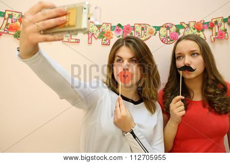 Two young girls with paper red lips and black mustache on a stick take pictures of themselves near the wall with the inscription happy birthday
