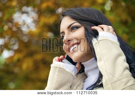 Happy beautiful brunette woman calling by phone in autumn park
