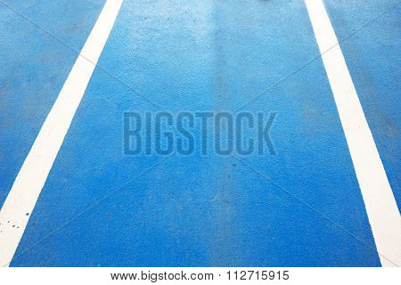 Closeup of blue running race track with two white rubber lines.