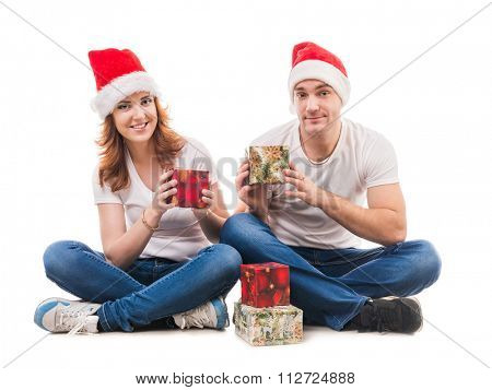 young couple in red hats hugging on the floor isolated on white background